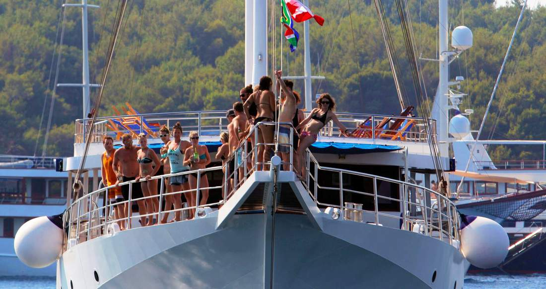 A group of people hanging out on the bow of a yacht with one girl hanging off and posing for the camera.