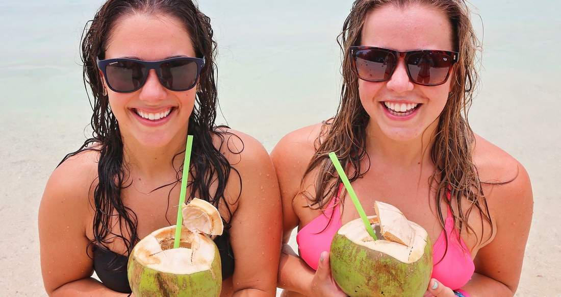 Two girls hold coconut drinks up and smile.
