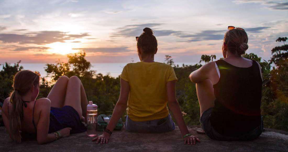 Three girls watch the sunset in the Philippines