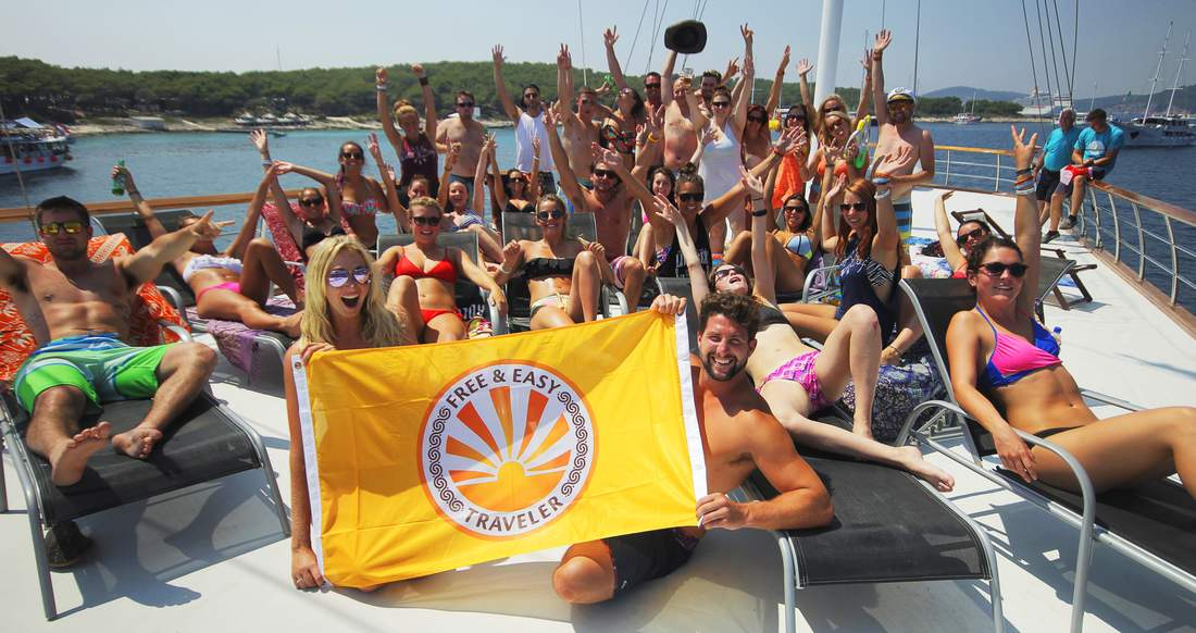 A group of young people posing on a yacht holding a Free and Easy Traveler flag.