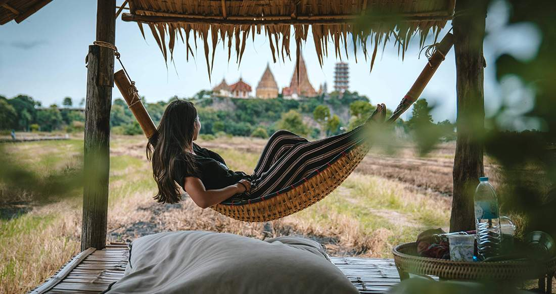 Girl in a hammock with a view of a temple in Thailand
