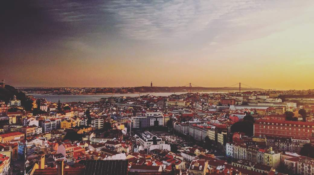 beautiful view of the sun setting over the city of lisbon portugal