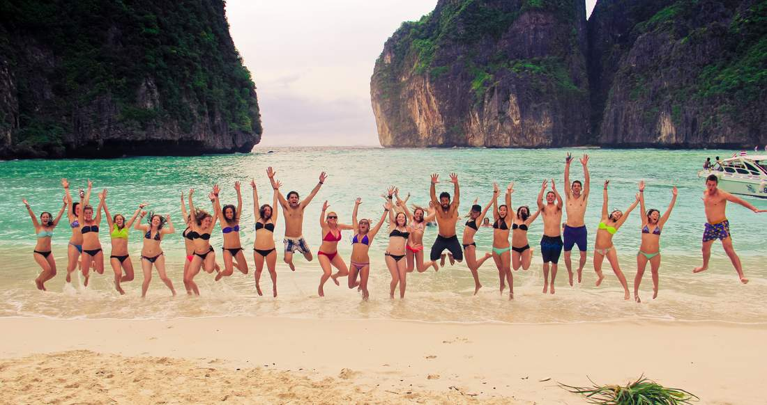 Group of travelers jumping up on Maya Bay beach in southern Thailand