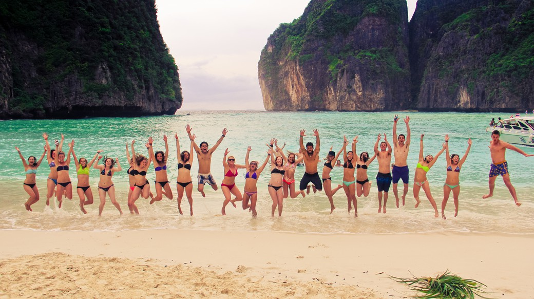 Group of travelers jumping up on May Beach in Southern Thailand