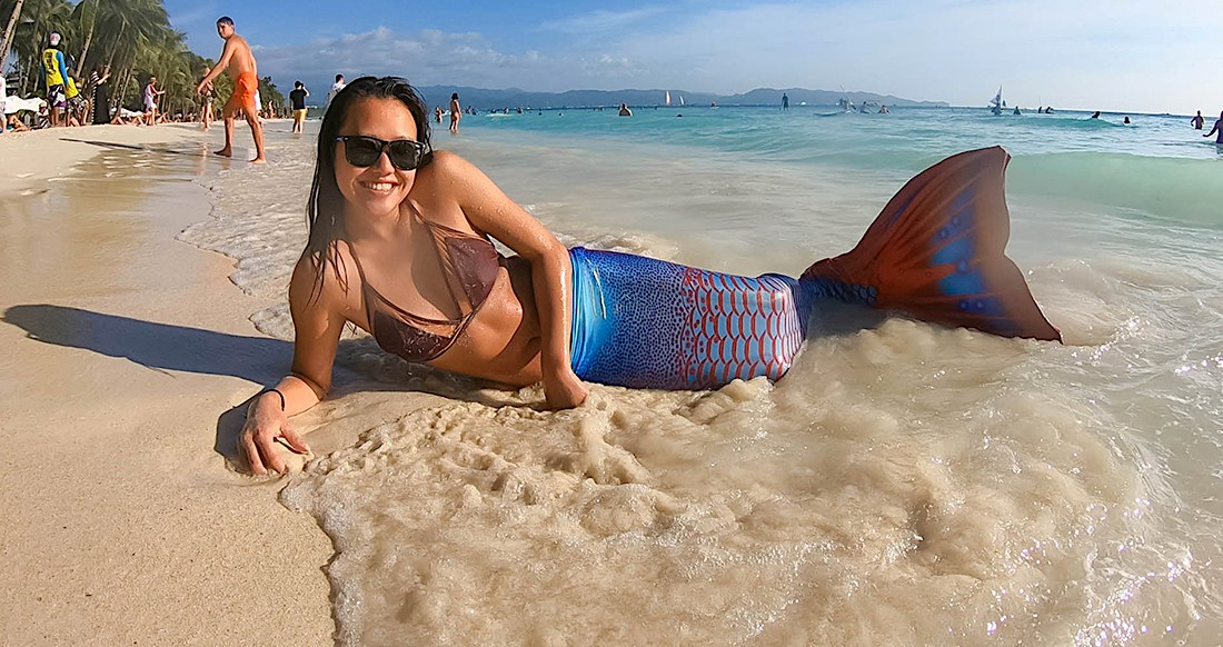 Girl on the beach with a mermaid tail on in the Philippines