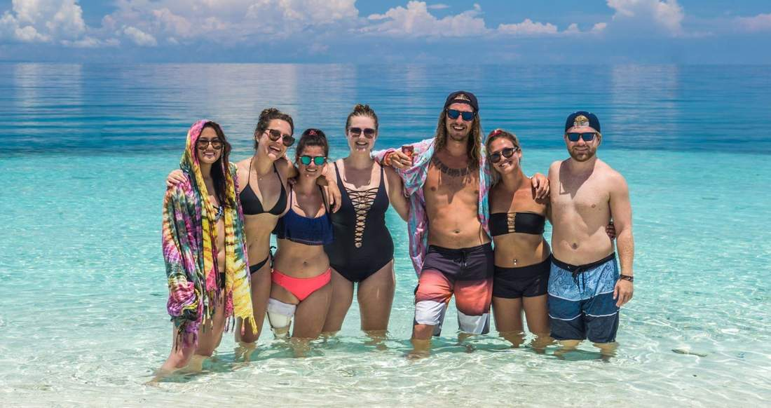 A group of travelers standing in the ocean in the Philippines
