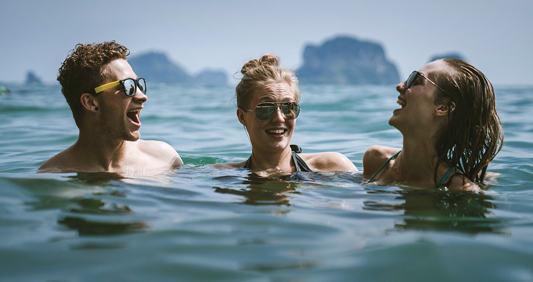 Three people laughing in the ocean in Thailand