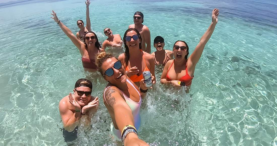 A group of travelers take a selfie in the ocean in the Philippines