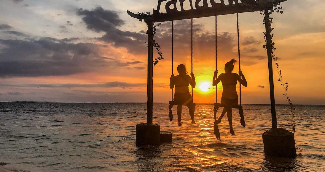 two girls on swings in the ocean while the sun sets in Indonesia