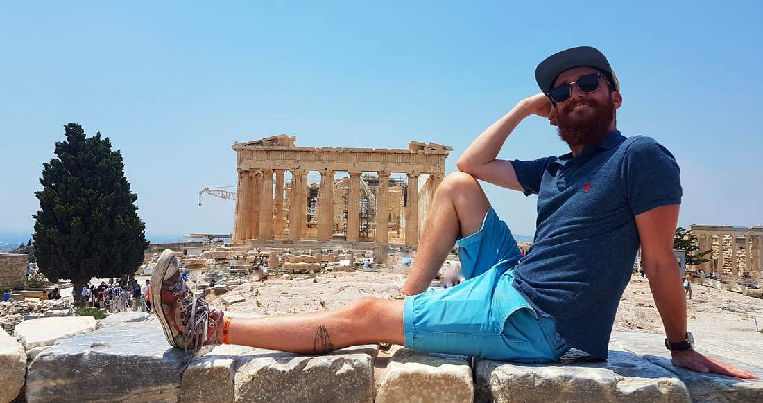 Traveler posing in front of the parthenon in Athens Greece