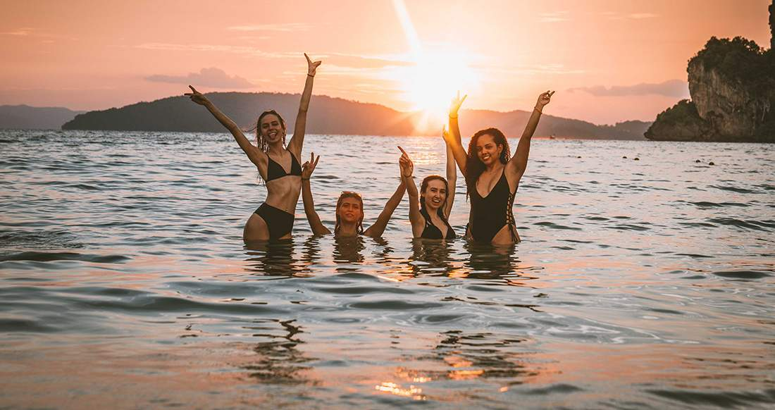 Girls in the ocean while the sun is setting at Railay beach Thailand
