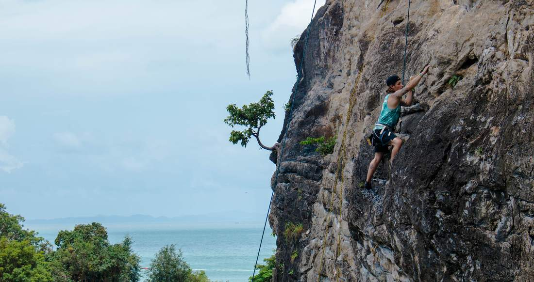 A young man rock climbs in the tropics.