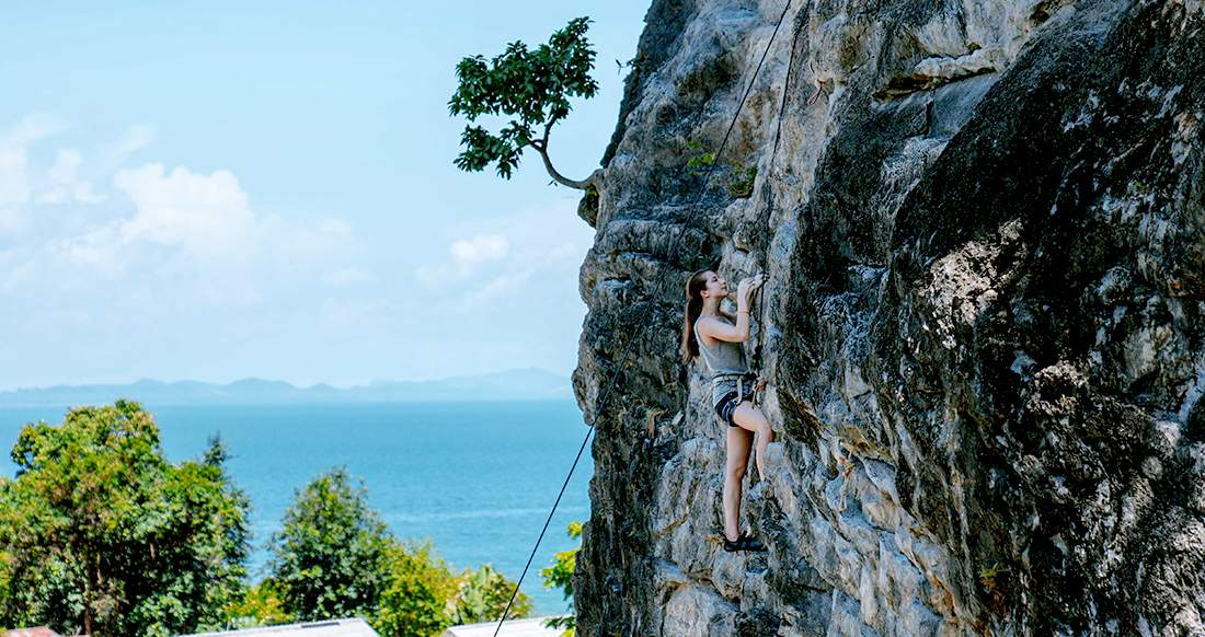 Traveler climbing a rock face in Railay, Thailand