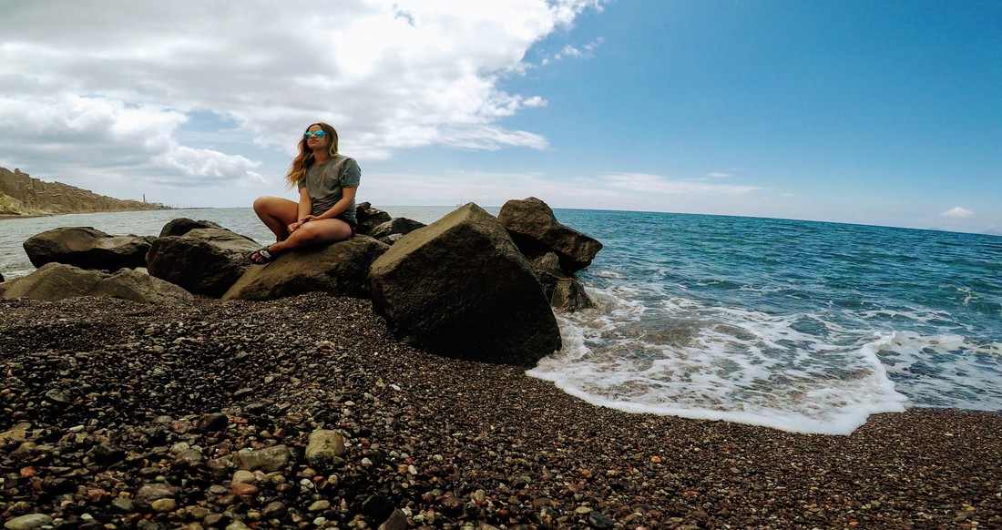 girl sitting on a rocky beach in Greece