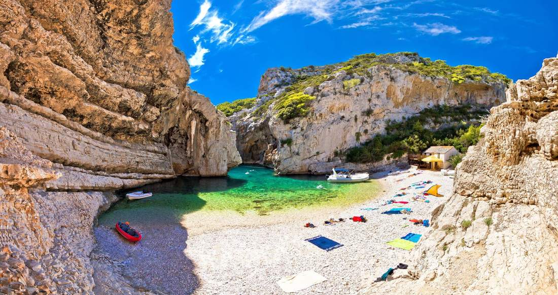 A beautiful secluded beach enclosed by rock walls.