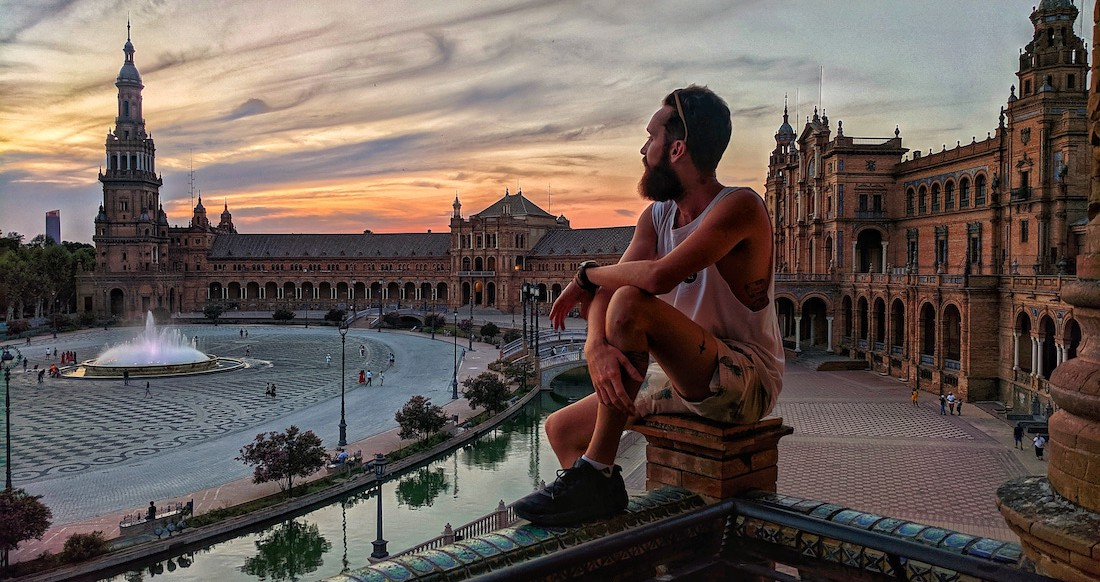 A traveler watches sunset at plaza de espana