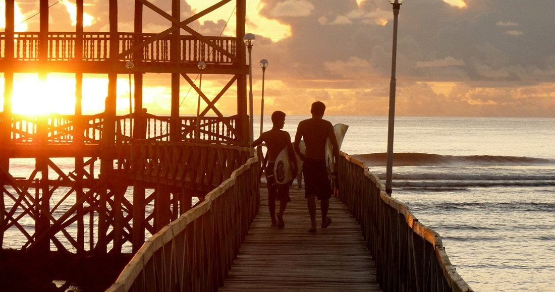 Two travelers walking along a boardwalk while the sun sets in the Philippines