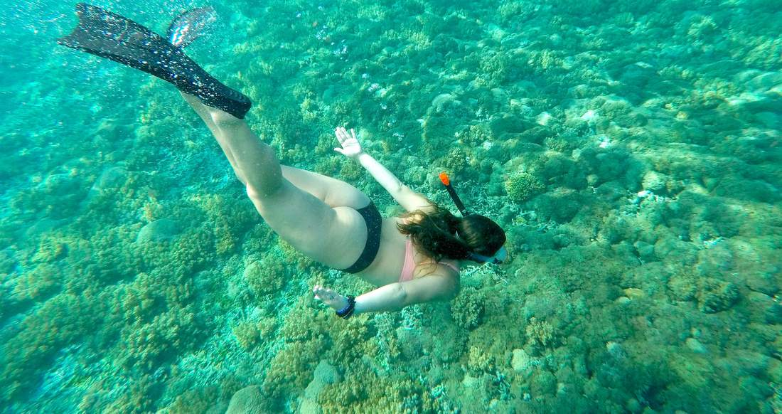 An underwater shot of a girl snorkelling.