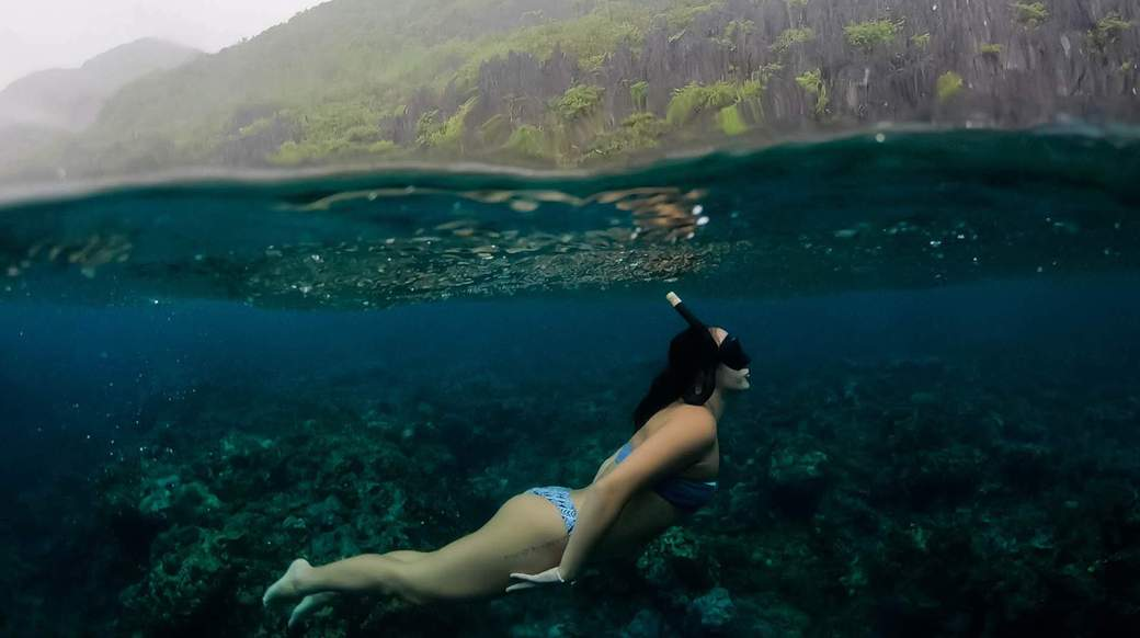a girl snorkelling underwater in the Philippines