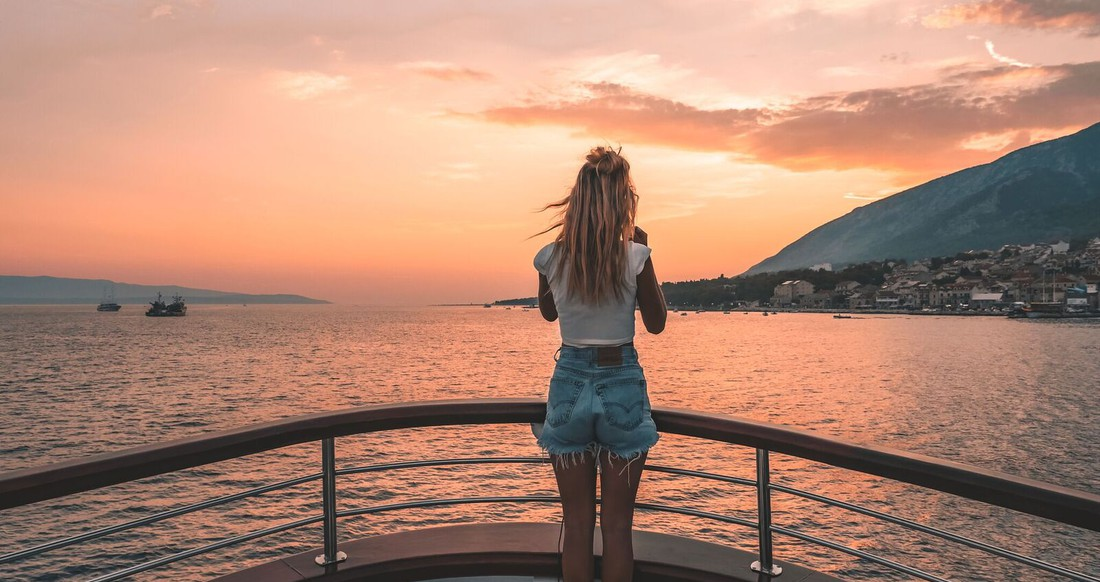 A girl stands at the bow of a yacht looking out at the sunset.