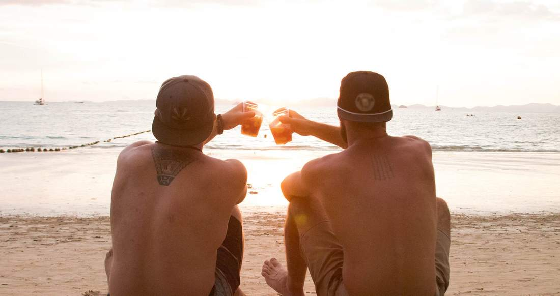 Two guys toast their fruity cocktails to a sunset on the beach.