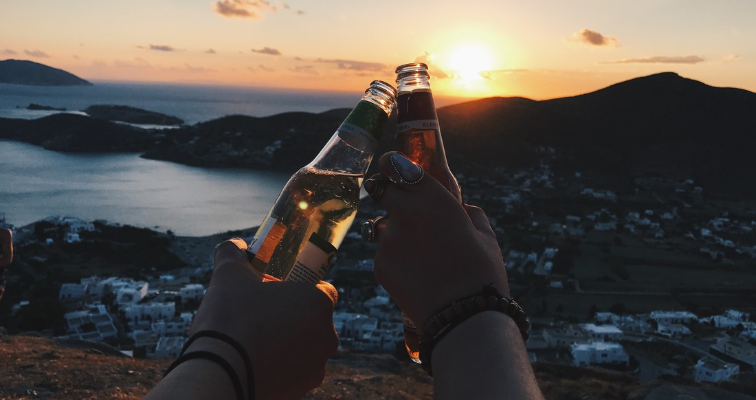 Two people clinking their beer bottles as the sun sets in Ios Greece