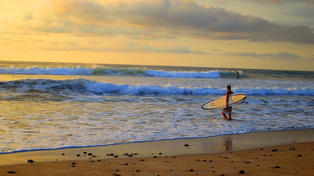 A dude standing on the beach with his surfboard as the sun sets in Costa Rica