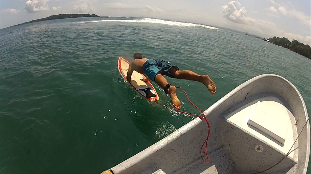 dude jumping into the ocean from a boat with a surfboard in panama