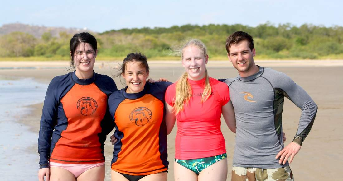 A group of travelers pose on the beach in surfing outfits.