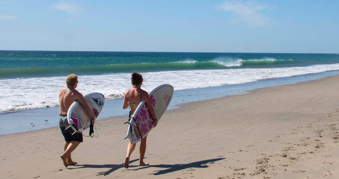 A couple walk along the beach holding surfboards as a wave curls in front of them.