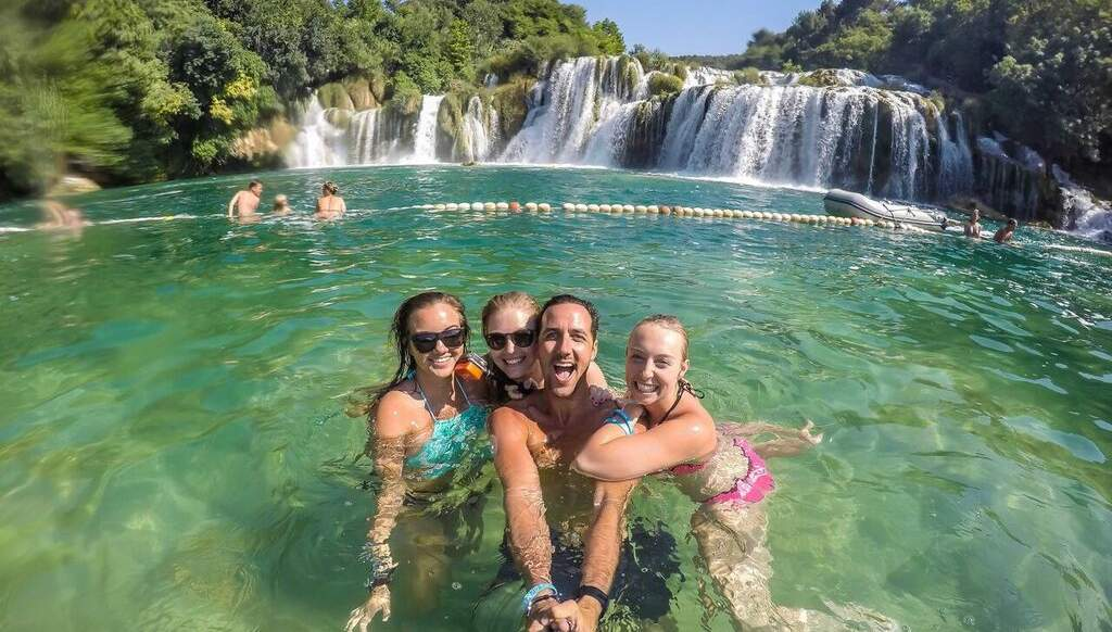 A man and three women are swimming in a pool in front of a waterfall.