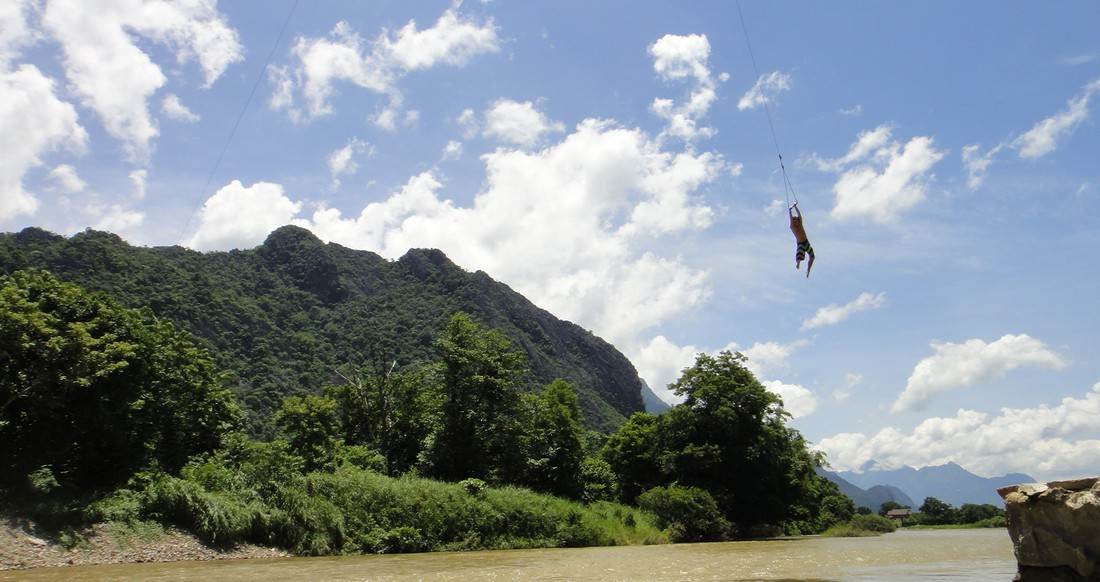 A man swings into the river in Laos