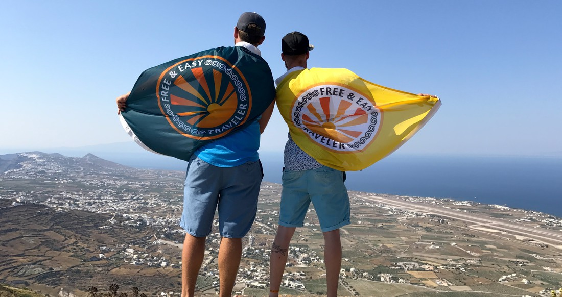 two guys looking at the view with flags on their backs in Greece