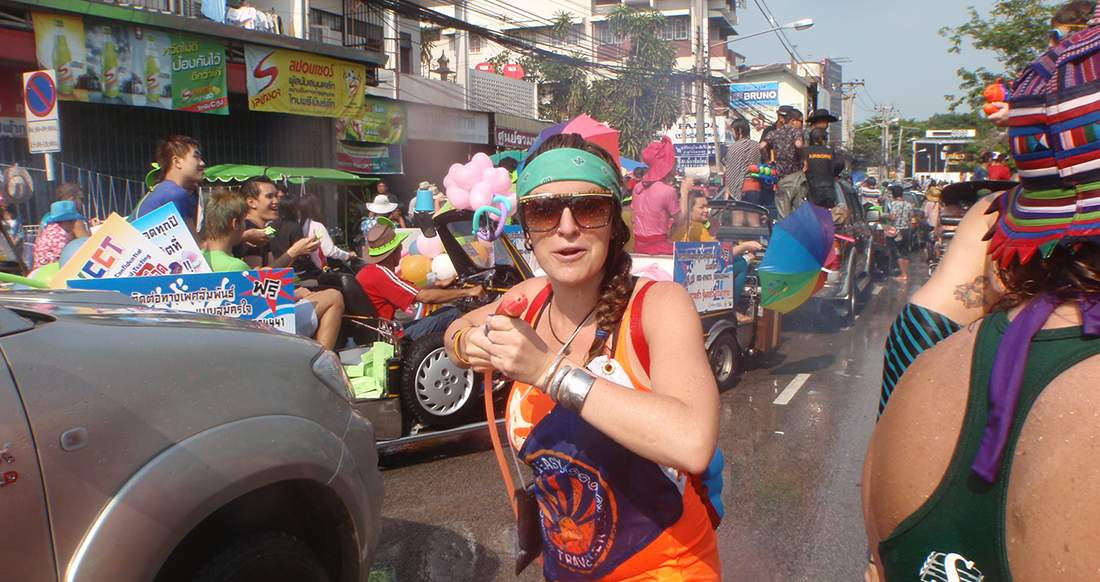 traveler participating in Songkran by splashing people with water