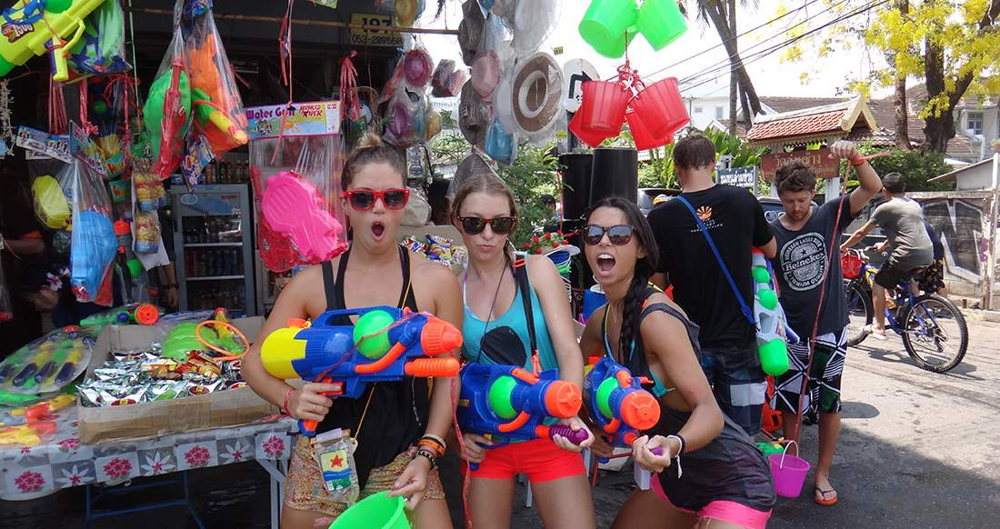 three girls holding super soakers getting ready for Songkran in Chiang Mai