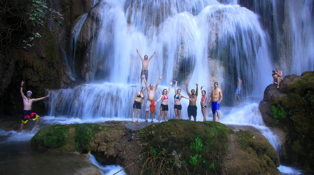 A group of travelers standing under a waterfall in Laos