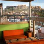 View of the Acropolis from a roof top bar with bright orange seating and floor to ceiling windows.