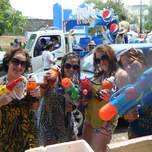Four girls holding water guns ready for songkran.
