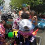 A group of people on the back of a truck receive a bucket of water in their faces.