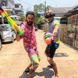 Two snarling guys pose with huge brightly coloured water guns.