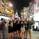 A group of people pose on the middle of a busy street in bangkok.