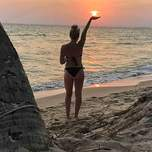 girl standing on a beach in Thailand as the sun sets