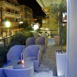 Comfortable candlelit tables line a balcony over looking a small apartment lined street