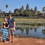 two travelers posing in front of Angkor Wat in Cambodia