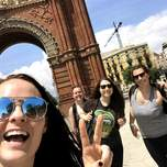A group of three woman smile and pose in front of the arc de triomf.