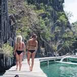 Two girls in bikinis walk along a boardwalk in a tropical paradise.