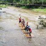 A group of travelers ride down a river on a long bamboo raft.