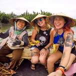 Two girls and an elder Vietnamese woman on a basket boat.