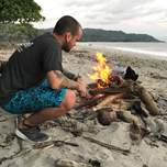 A man crouches down in front of a fire he's building on a beach.
