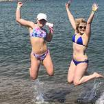 Two girls in bikinis jump for joy in the Mediterranean.